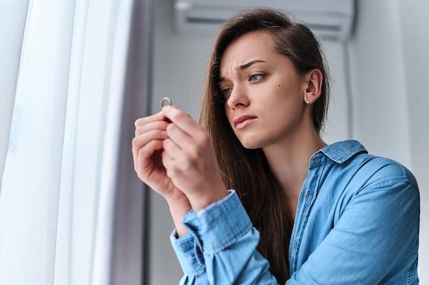La donna divorziata triste sollecitata turbata sola tiene in mano l'anello d'oro e si siede da sola a casa durante i problemi nella vita e la crisi nelle relazioni. rompere il matrimonio