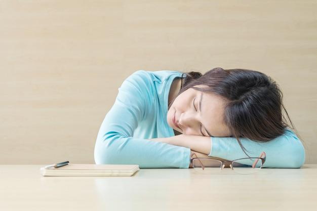 La donna dormiva mentendo sulla scrivania dopo aver provato a leggere un libro nel tempo di riposo