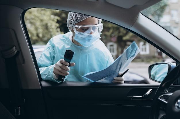 La donna dottore usa una pistola a termometro a infrarossi per controllare la temperatura corporea