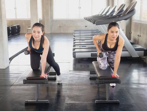 La donna due sta esercitandosi con un dumbbell in ginnastica