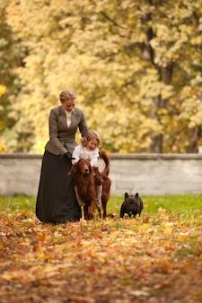 La donna e il bambino con i vestiti vintage passeggiano nel parco con i cani