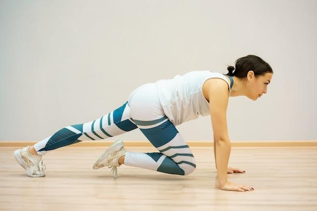 La donna è impegnata nel fitness a casa sul tappeto blu, in abiti sportivi. allenamento e stretching a casa