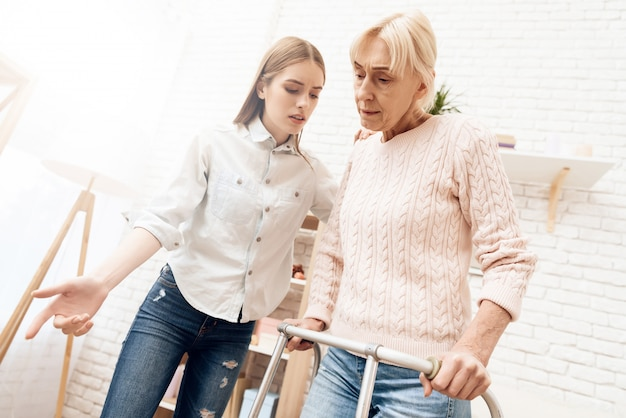 La donna è in piedi con l'aiuto del deambulatore. la ragazza è vicina, aiutando