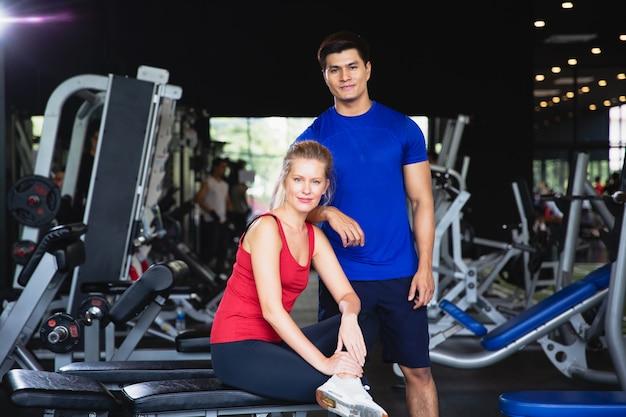 La donna e l'uomo di forma fisica con gli abiti sportivi che si siedono e esaminano la macchina fotografica dopo l'esercizio allo sport della palestra con lo spazio della copia, il bodybuilding sano di allenamento delle coppie, lo yoga e la forma fisica elaborano il concetto di sanità