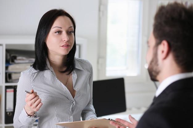 La donna e l'uomo graziosi del brunette discutono nell'ufficio che si siede alla tabella