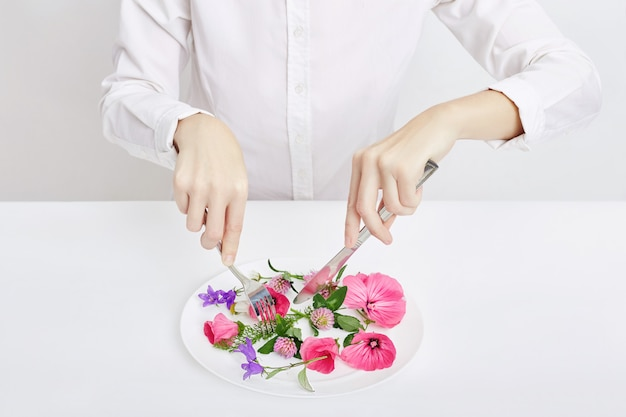 La donna e la bella molla fiorisce in piatto, mani