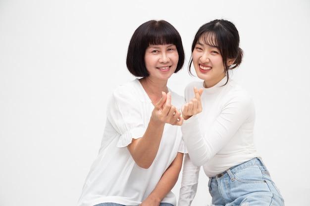 La donna e la figlia senior asiatiche felici con il mini cuore firmano insieme isolate