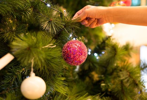 La donna è la mano che decora un albero di natale con la palla
