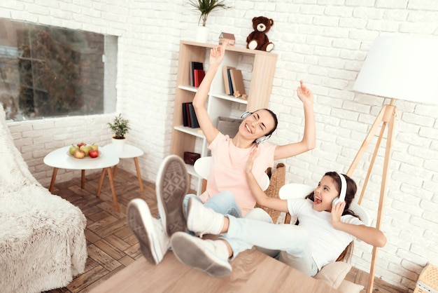 La donna e la ragazza ascoltano musica con le cuffie e si rilassano.