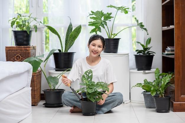La donna è seduta e pianta alberi in casa.