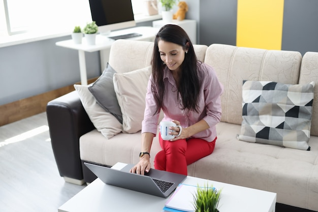 La donna è seduta sul divano tenendo la tazza in gamberi e con l'altra mano digitando sulla tastiera del laptop.