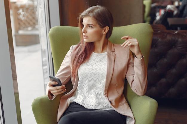 La donna elegante in una giacca rosa passa il tempo in un caffè