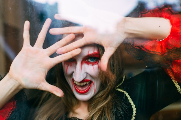 La donna emozionale in costume della strega posa dietro la finestra.