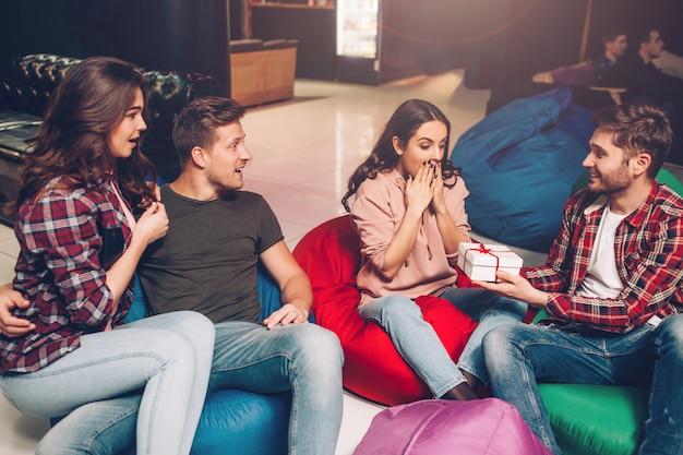 La donna emozionante felice del oyung si siede sulla borsa gonfiabile. guy dà la sua scatola bianca con regalo. lei è felice. le sue amiche guardano e sorridono.