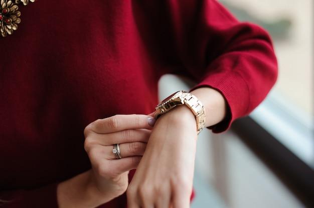 La donna esamina l'orologio che aspetta l'aereo all'aeroporto