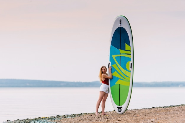 La donna esile sopra sta sulla spiaggia con il bordo del sup della pagaia con i bei colori del tramonto o dell'alba