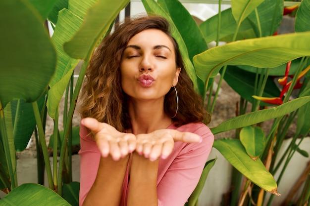 La donna europea con i capelli corti ricci invia il bacio dell'aria alla telecamera.