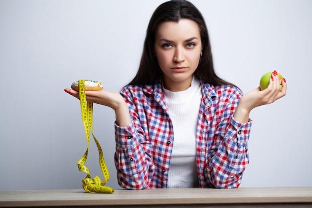 La donna fa una scelta tra cibo sano e nocivo