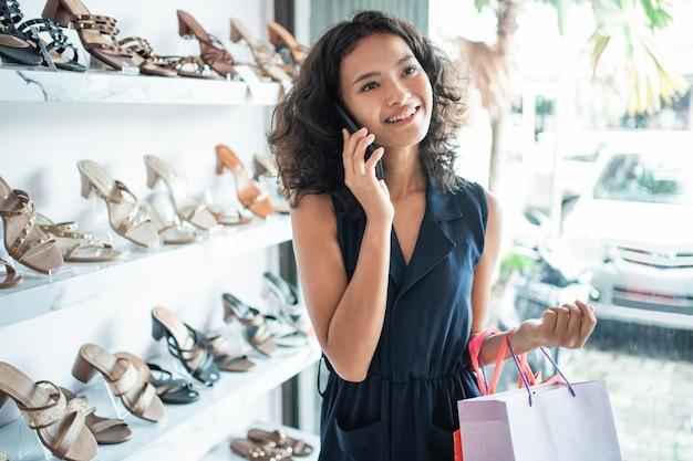 La donna fa una telefonata mentre fa la spesa