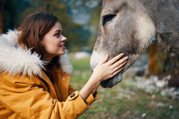 La donna felice abbraccia un asino in primo piano della natura