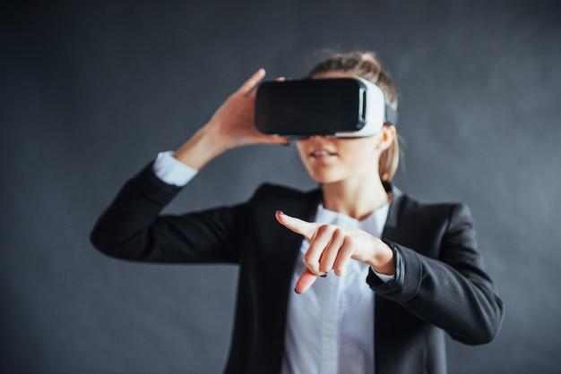 La donna felice acquisisce esperienza nell'uso delle cuffie per realtà virtuale con occhiali vr