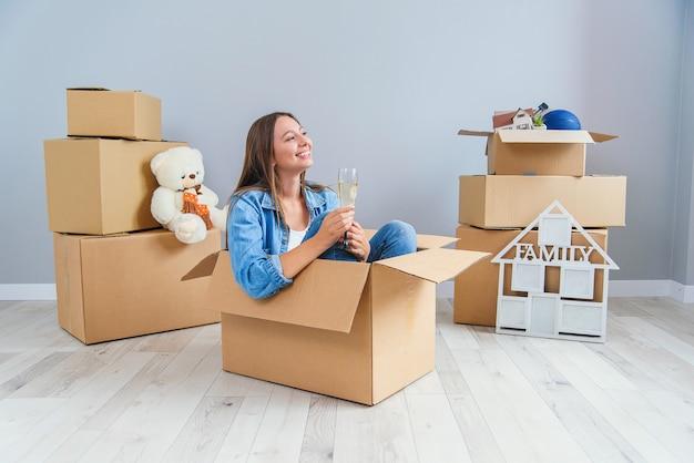 La donna felice beve champagne da un bicchiere, mentre seduto all'interno di una scatola di cartone nel nuovo appartamento.