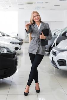 La donna felice che tiene l'automobile chiude a lungo la chiave