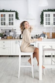 La donna felice di risata si siede con una tazza in una cucina luminosa