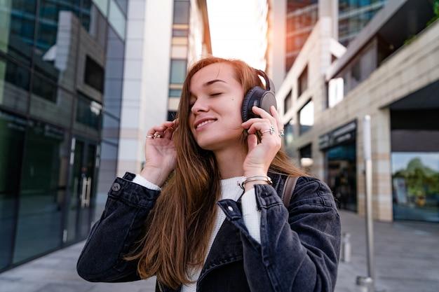 La donna felice gode della musica in cuffia senza fili mentre cammina per la città