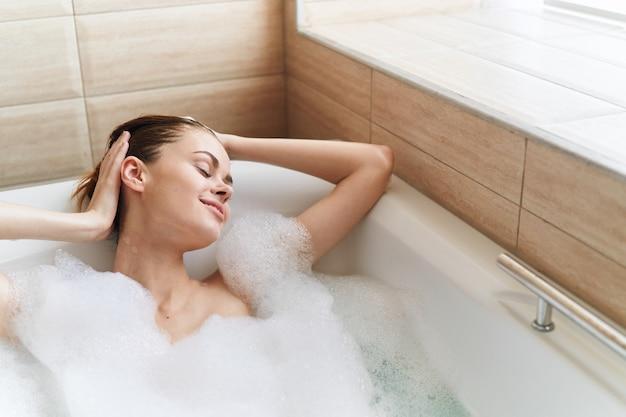 La donna felice gode di relax in bagno e schiuma bianca