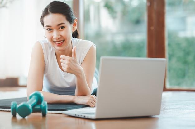 La donna felice ha finito la lezione di allenamento online a casa