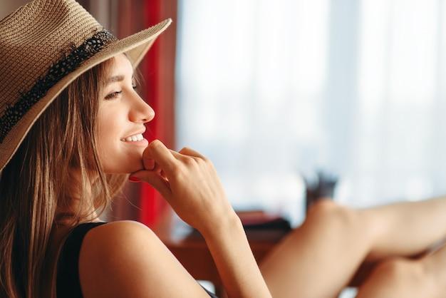 La donna felice ha gettato le gambe sul tavolo, sogna un concetto di vacanza, viaggio sognando ad occhi aperti