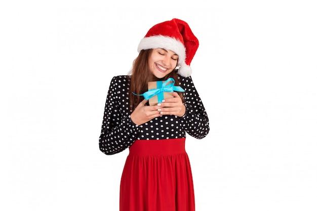 La donna felice in cappello di natale abbraccia un regalo avvolto in carta riciclata.