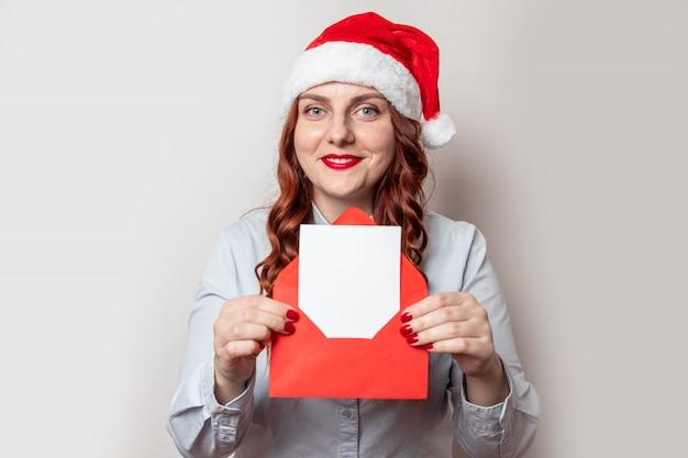 La donna felice in cappello di sanya pensa a natale con la lettera o la lista di desiderio in busta rossa in mani alla notte di natale