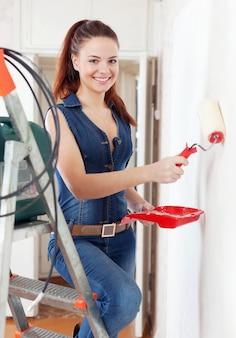 La donna felice in tuta vernicia la parete