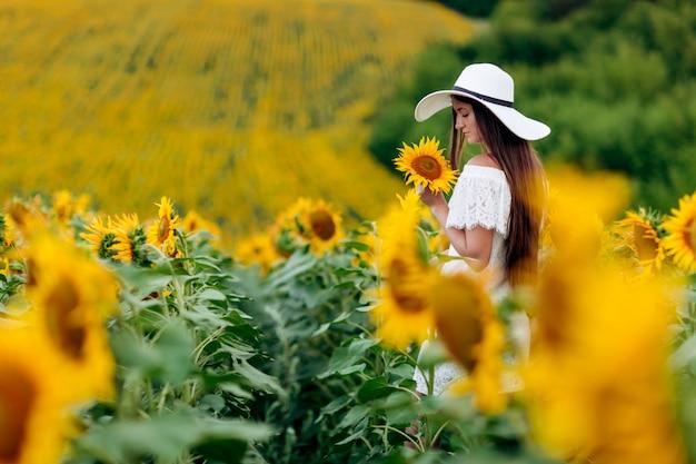 La donna felice in un vestito bianco e cappello in un campo di girasoli gode la luce del sole. passeggiata estiva sul campo di girasoli di una giovane ragazza. messa a fuoco selettiva