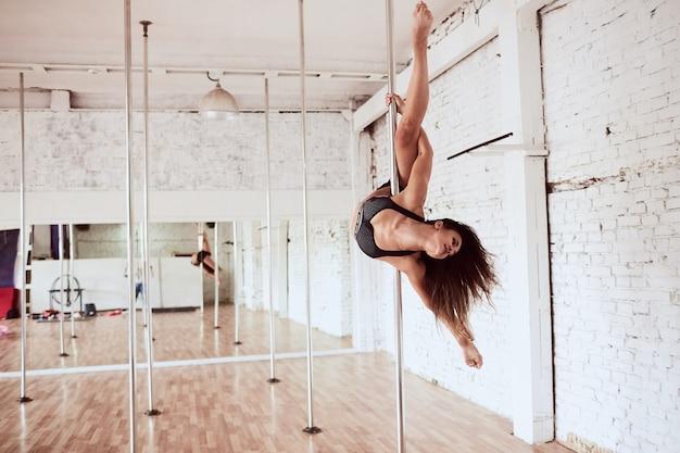 La donna felice in vestiti neri esegue il ballo o lo yoga intorno al palo nello studio