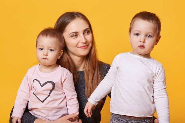 La donna felice, la madre ed i suoi bambini gemellati posa nello studio fotografico