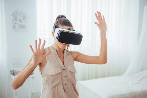 La donna felice ottiene esperienza nell'uso delle cuffie per realtà virtuale con occhiali vr in modo luminoso
