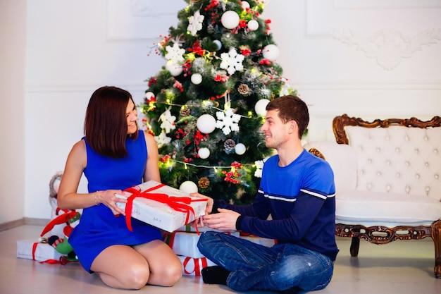 La donna felice ottiene il suo regalo di natale da suo marito. bella coppia seduta con doni vicino all'albero di natale
