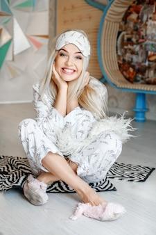 La donna felice ride e si siede in pigiama sul pavimento. maschera del sonno