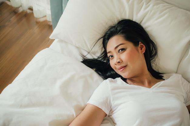 La donna felice si distende sul suo letto di mattina.