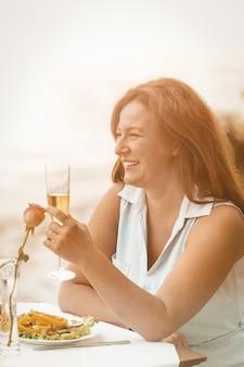 La donna felice sorride sollevando un bicchiere di vino o un champagne contro lo sfondo della spiaggia sabbiosa.