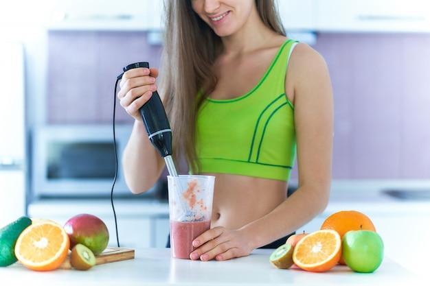 La donna felice sorridente di forma fisica in abiti sportivi prepara un frullato della frutta fresca facendo uso di un miscelatore della mano a casa nella cucina.