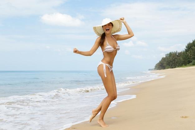 La donna felice sta camminando sulla costa del mare
