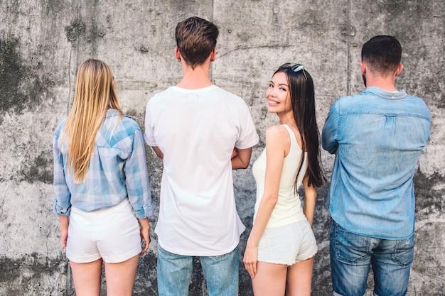 La donna felice sta guardando indietro e le sue amiche sono in piedi di fronte al muro