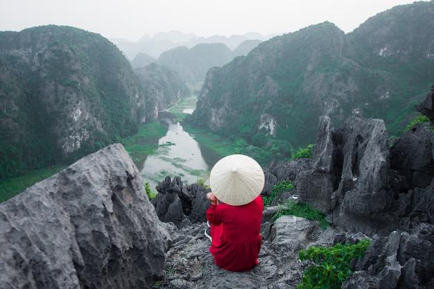 La donna felice sta sul picco della montagna a mua cave, ninh binh, vietnam alla sera, il soggetto è sfocato, scuro e rumore.