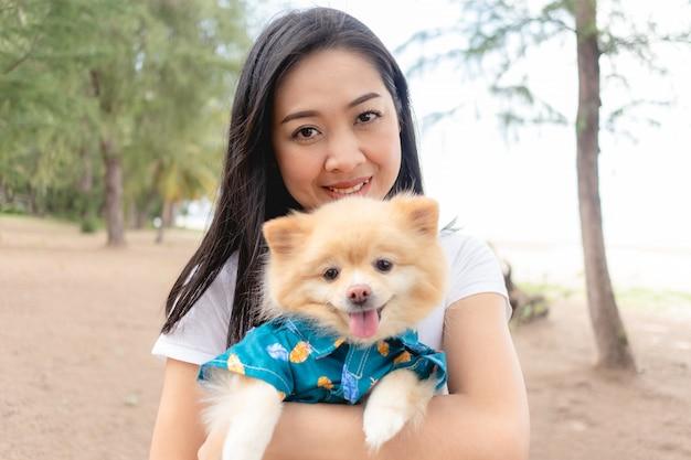La donna felice sta tenendo un cane pomeranian.