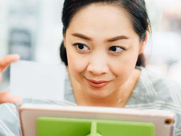 La donna felice sta usando una carta di credito bianca del modello per acquisto online sul ridurre in pani.