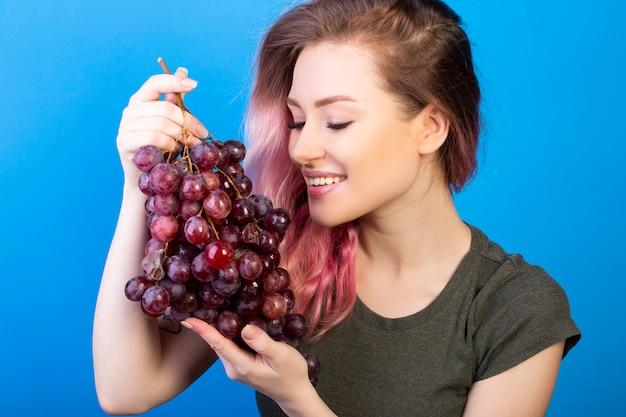 La donna felice tiene un grande mazzo di uva con entrambe le mani